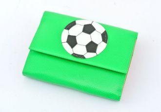 Portemonnaie mit Fussball auf grüner Blache